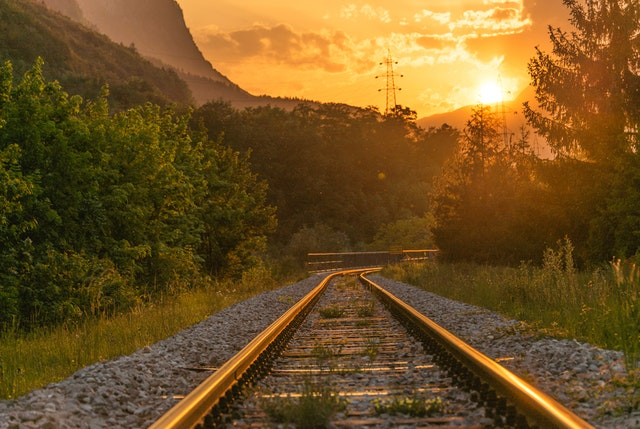 koleje a les při západu slunce
